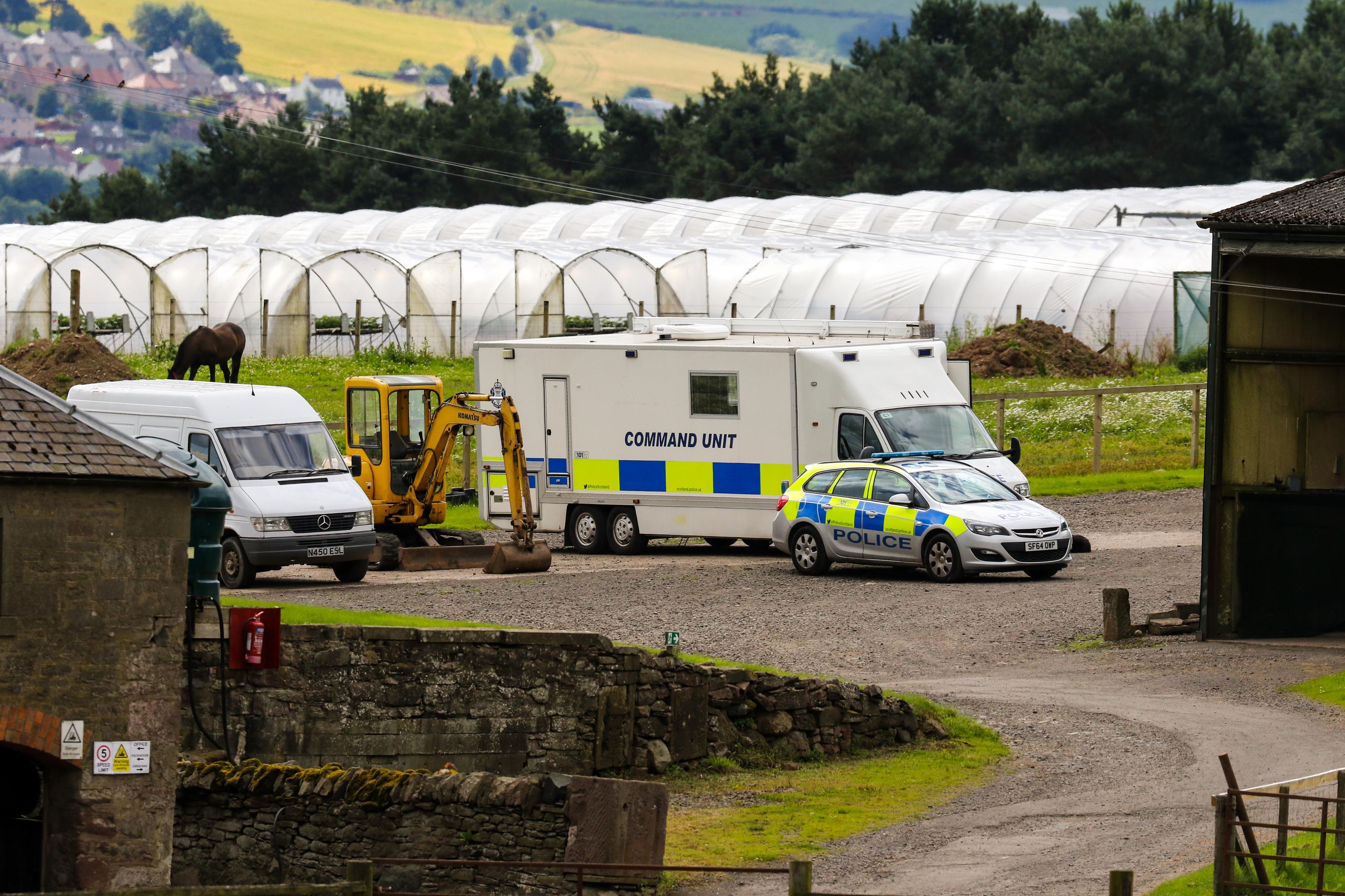 Police vehicles at the scene at Mains of Errol Farm, Errol, on Monday.