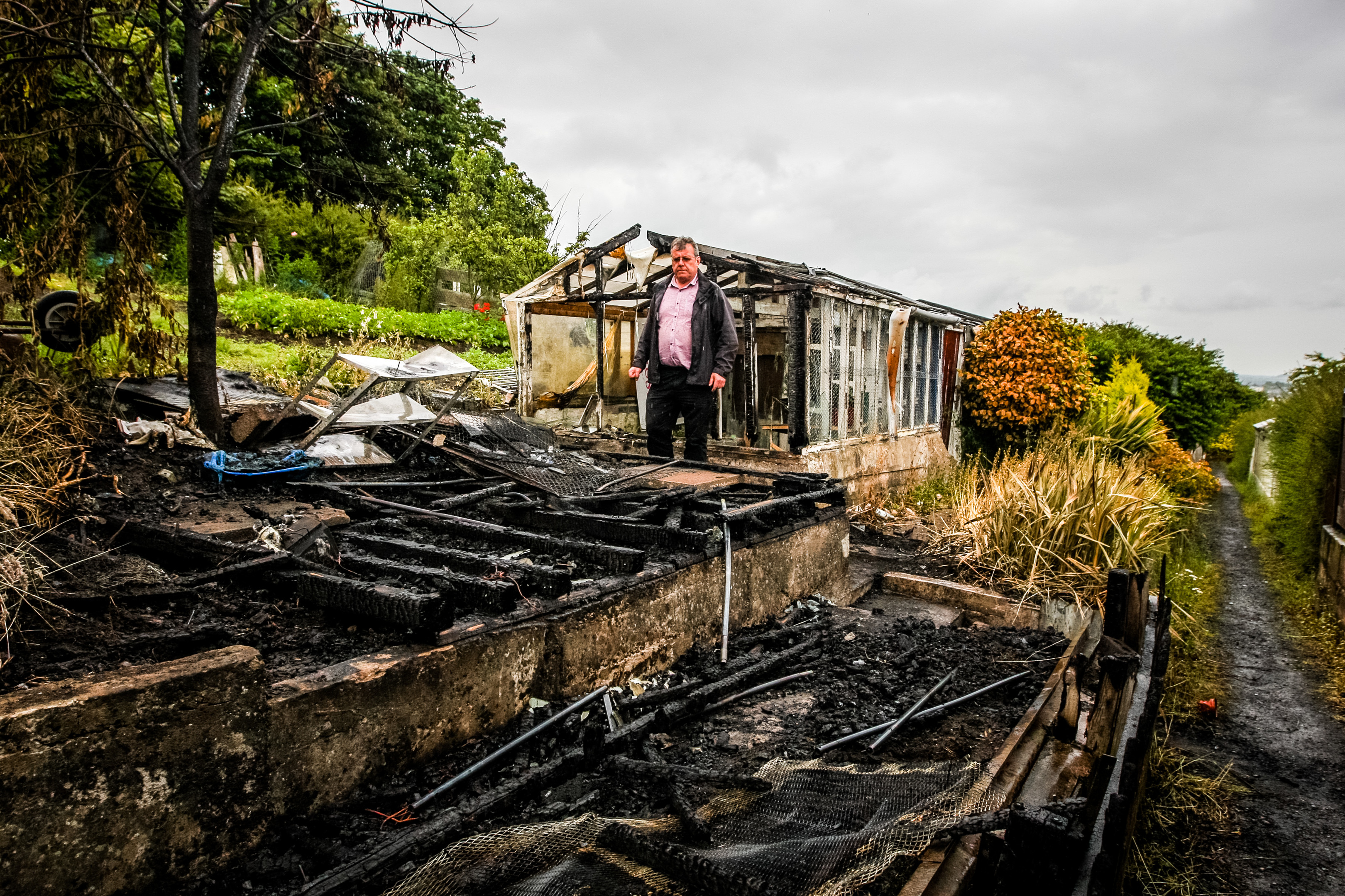 Gordon Robbie (chairman of  Kinnaird Garden Association Allotments) inspects the damage to the burnt out wreck of a shed.