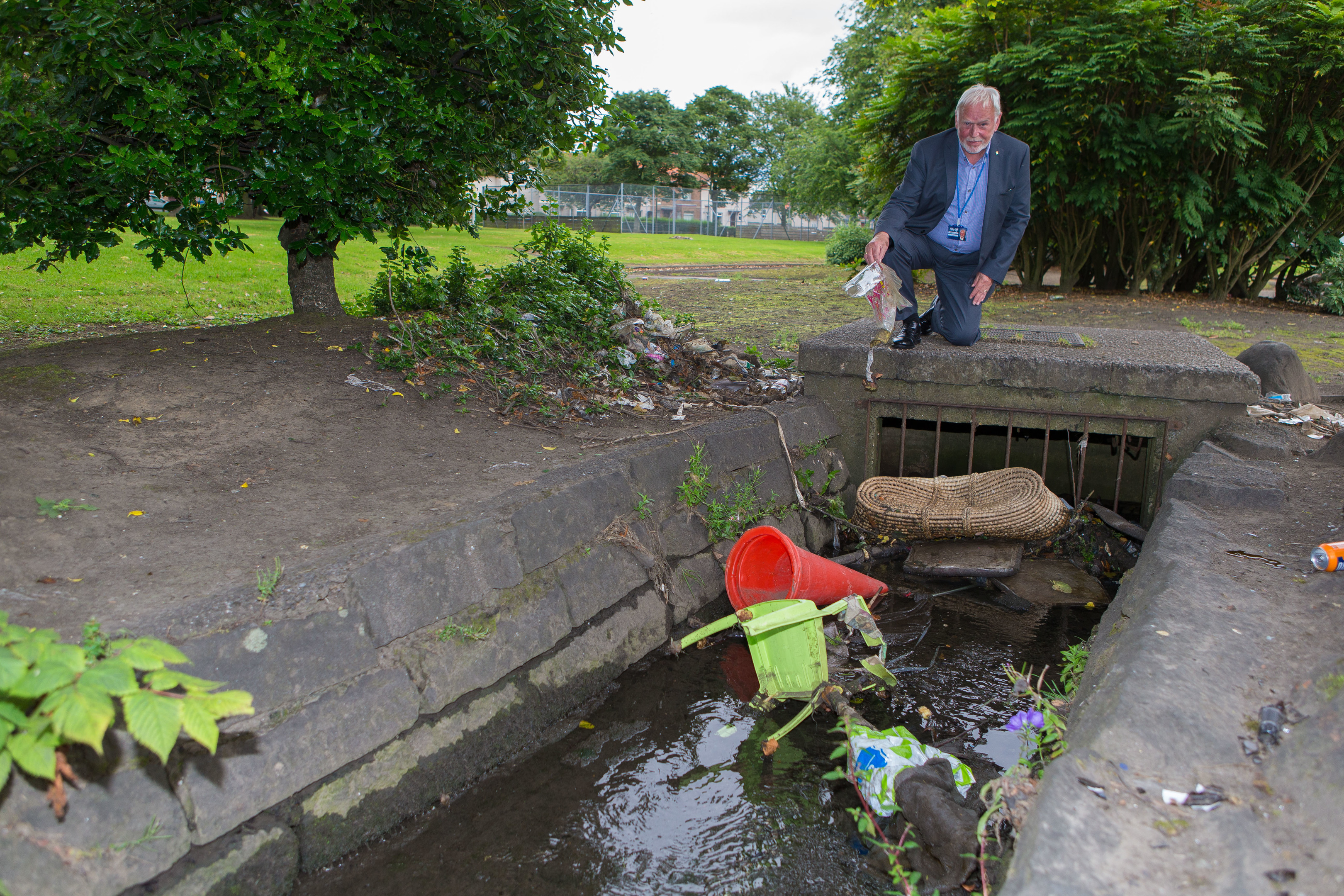 Councillor Stuart MacPhail surveying the rubbish in the burn at Adamson Avenue.