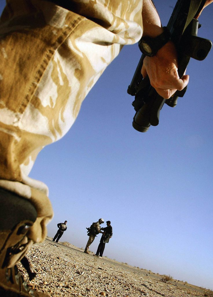 A British soldier attached to the Black Watch searches Iraqi men at a check-point in the desert near camp Dogwood, 25 miles south of Baghdad, in 2004.