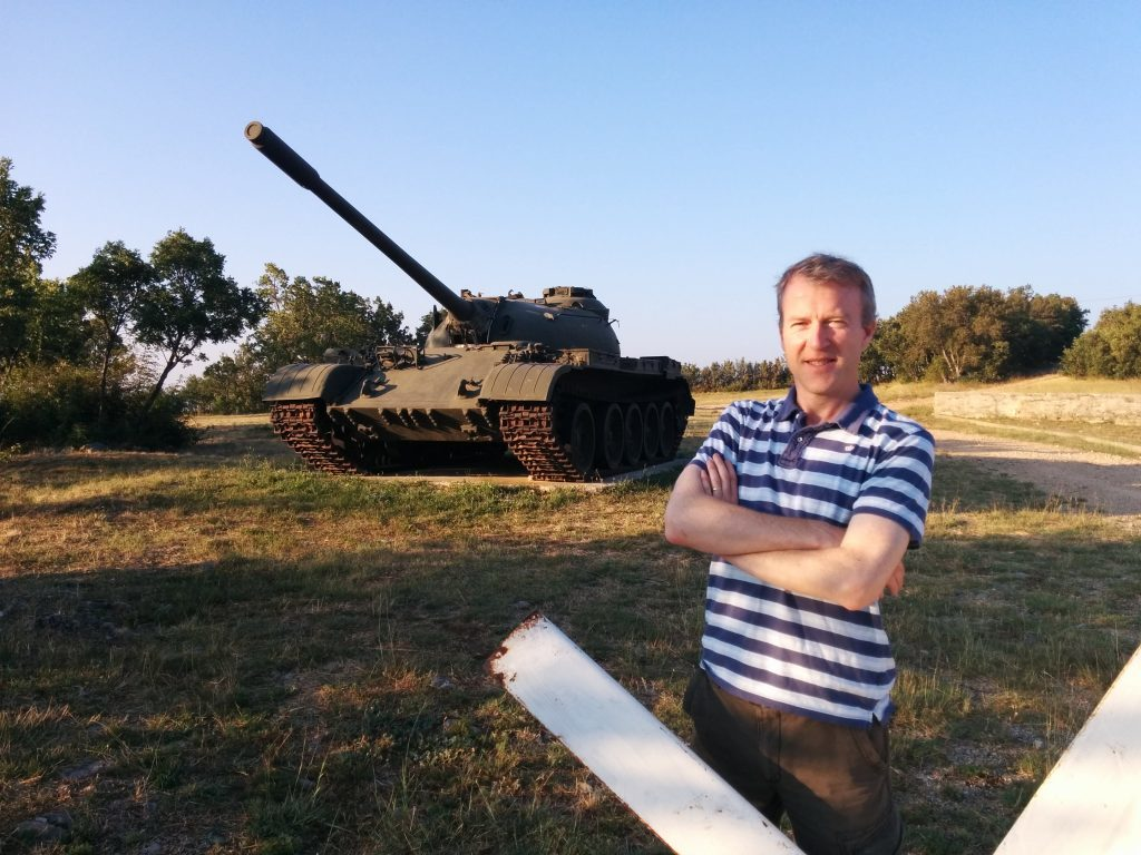 The Courier's Michael Alexander in front of a former Soviet-built TV2 tank at the Red Earth military base