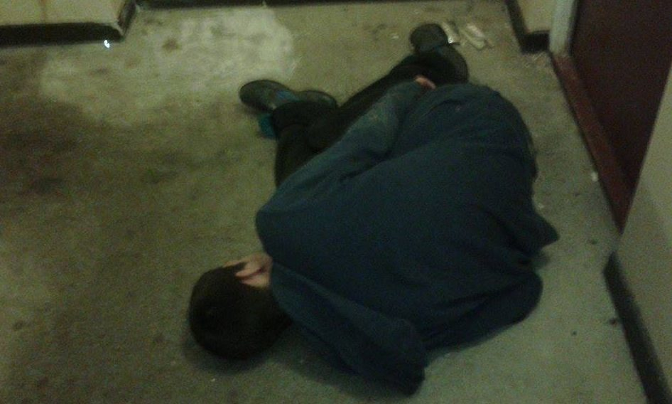 The shocking photo shows a young man collapsed near drugs paraphernalia (top right).