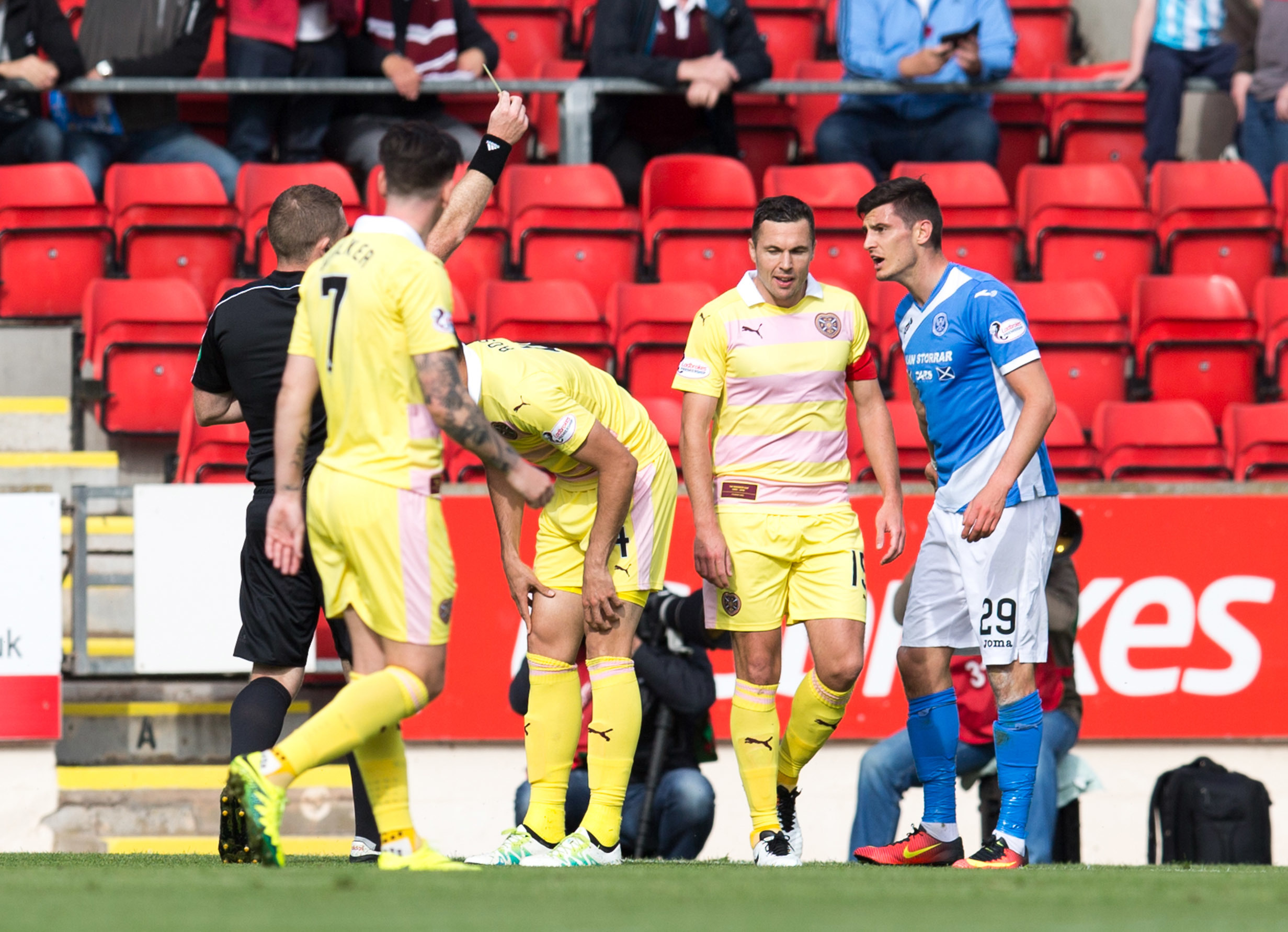 Referee John Beaton shows St Johnstone's Graham Cummins the yellow card.