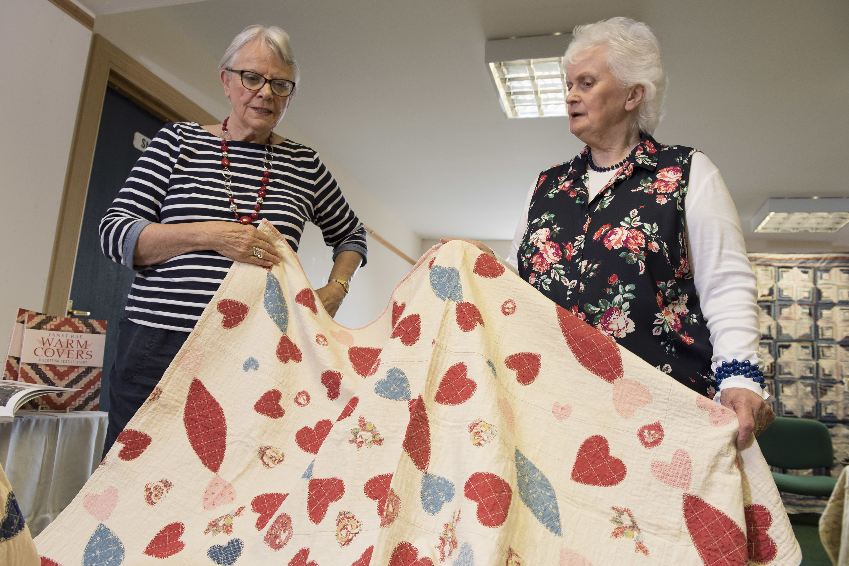 Author Janet Rae looks over Sandra Affleck's quilty at the Keeping the Thread event