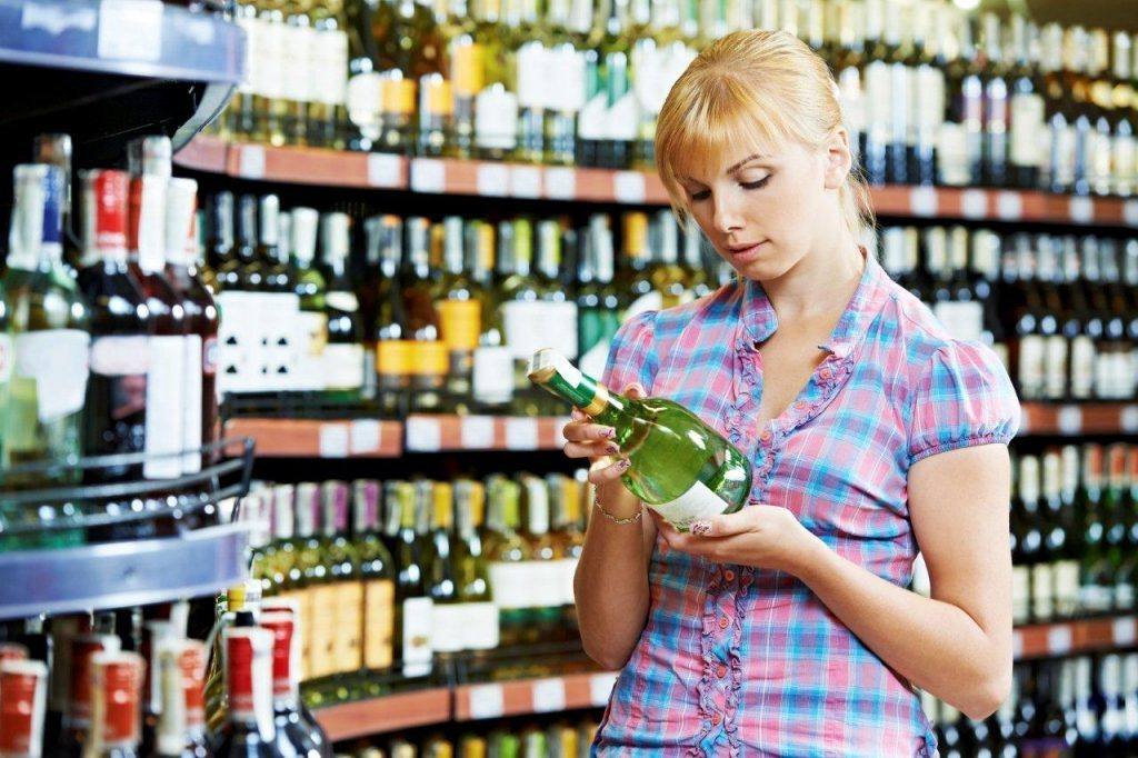 A woman browses a supermarket alcohol aisle. But what about the hangover?