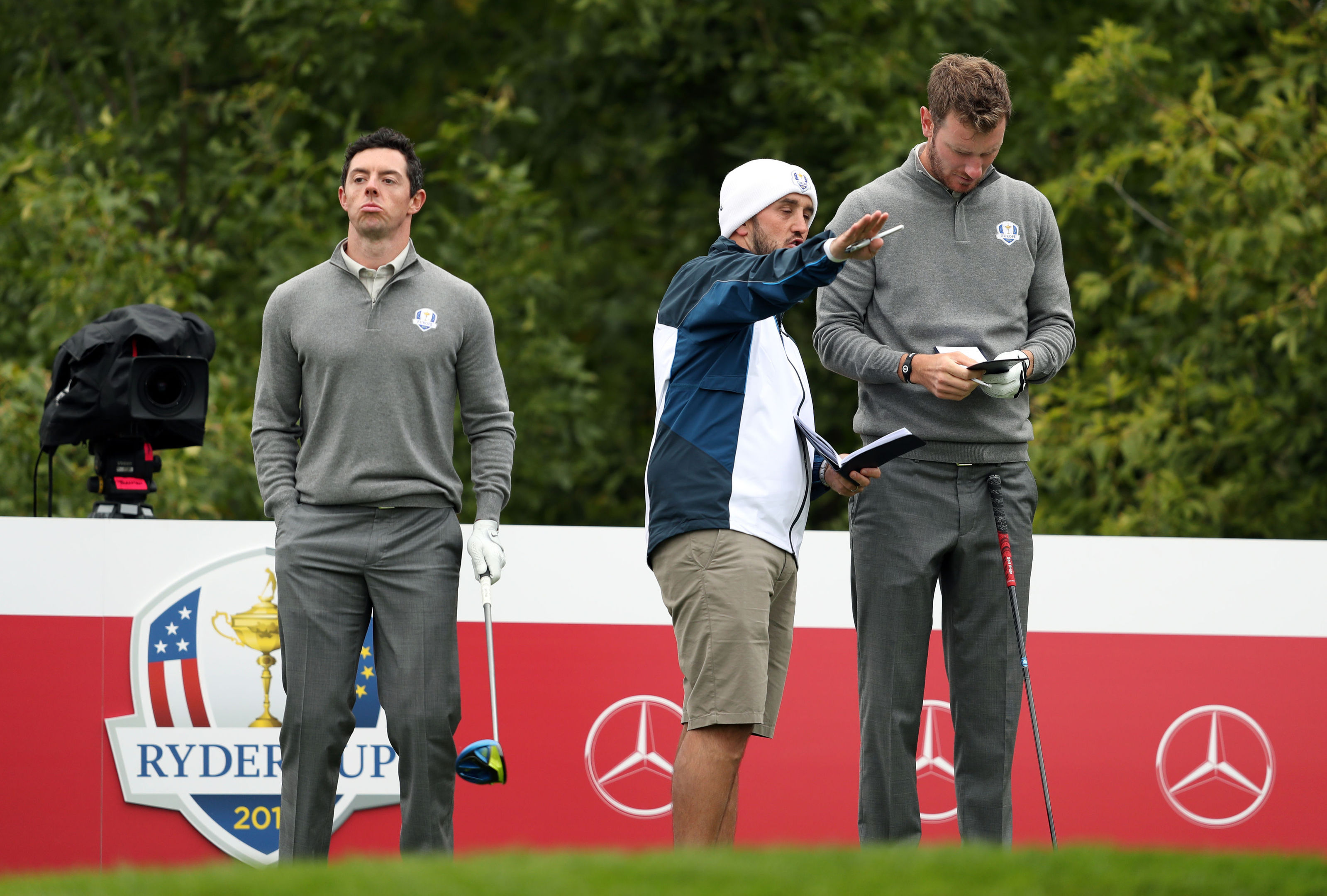 Chris Wood takes directions from Scottish caddie Mark Crane while Rory McIlroy waits during practice at Hazeltine.