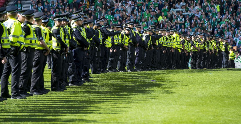 Police try to subdue Hibs fans as they rush the pitch to they celebrate their side's historic win