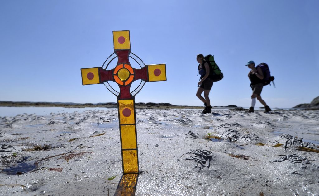Pilgrims make their way along a beach on Iona much as St Columba and his followers might have done on arrival there