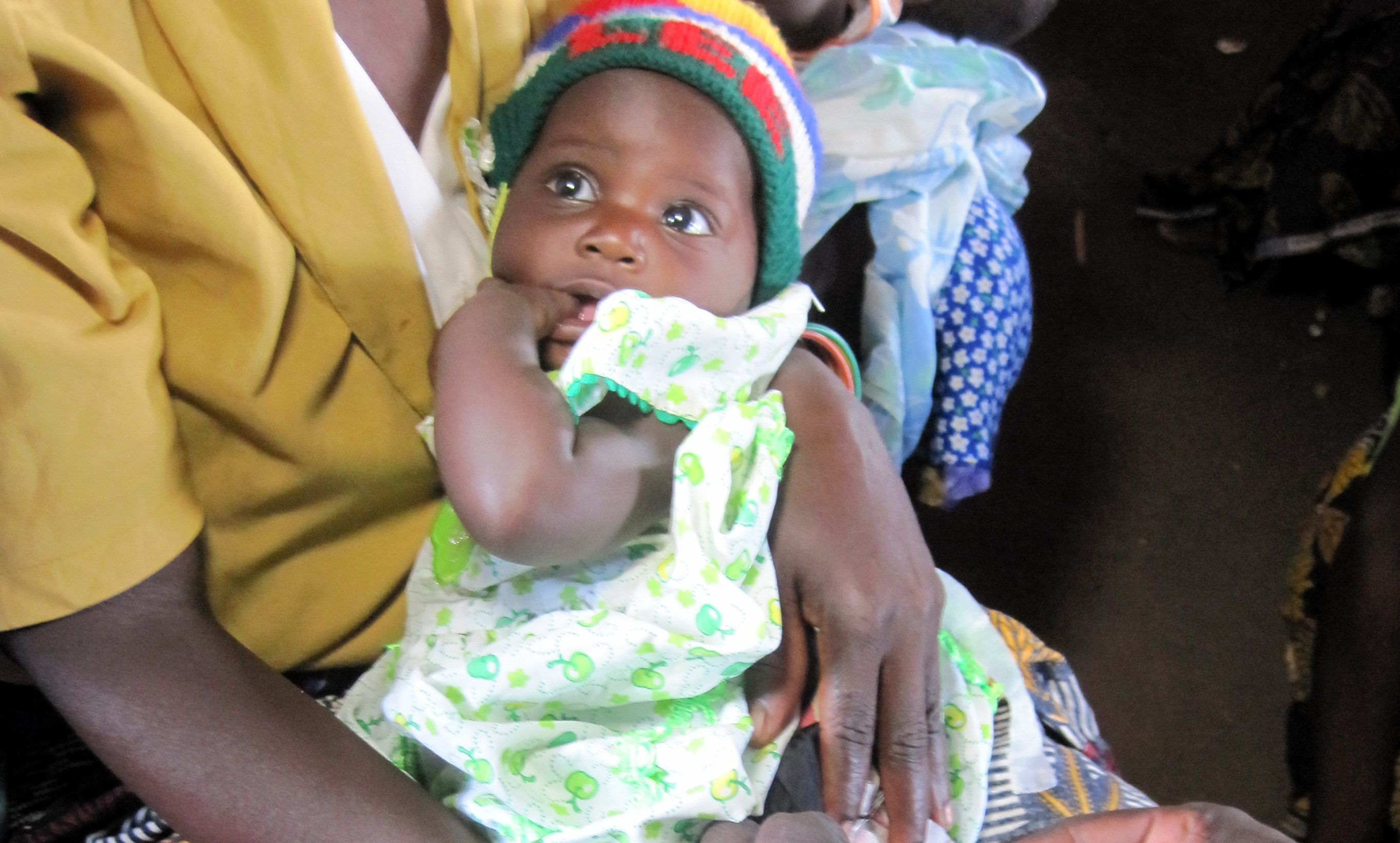 A mother holds her child as they are vaccinated by health workers in Malawi.