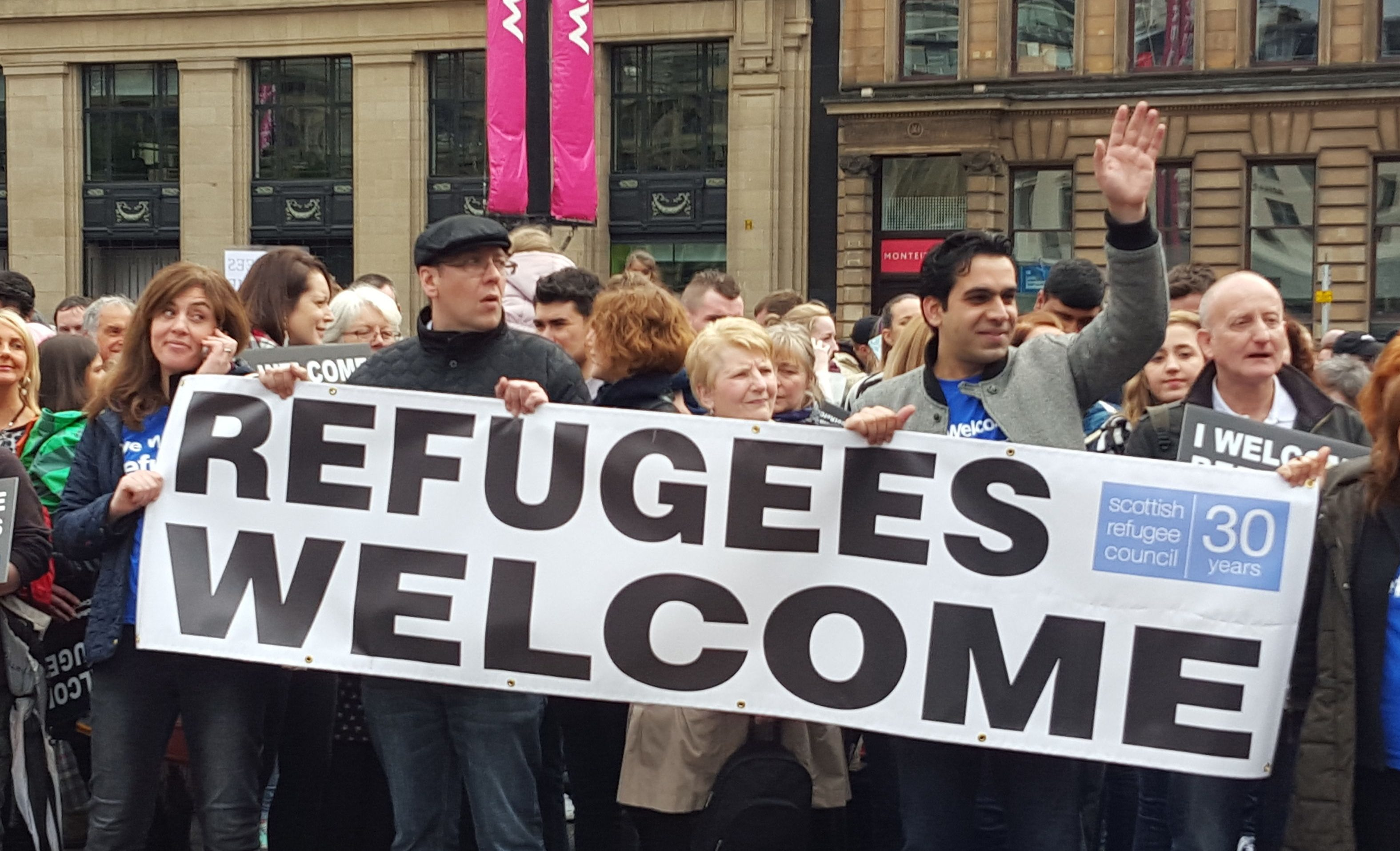 Members of the Scottish public carry a banner supporting the effort to accommodate refugees.