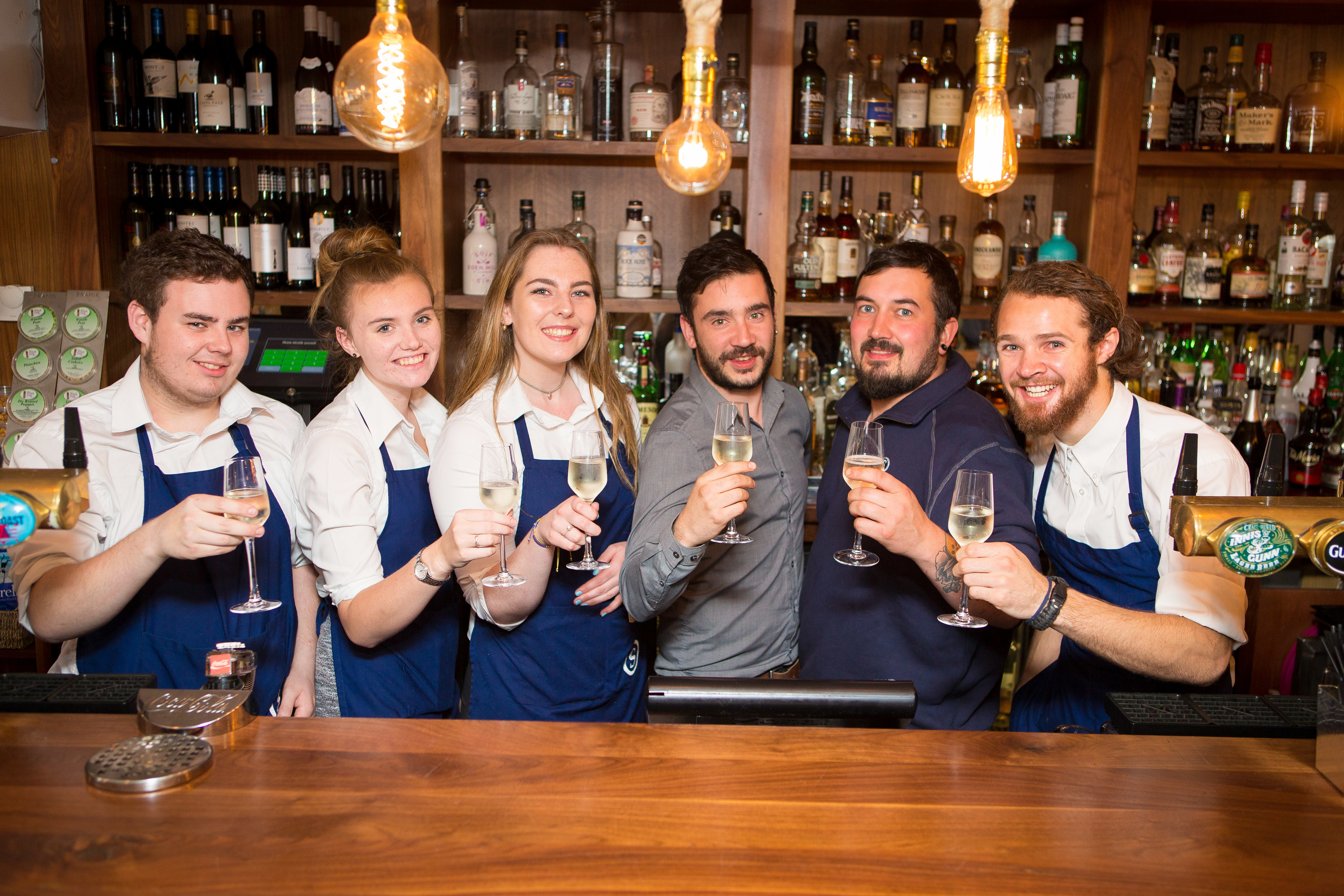 Staff members from Left: Sean Brown, Stephanie Guild, Sarah Salvesen, Jordan Dignan, Sian Linton and Tristan Riechel all celebrate the win with Prosecco.