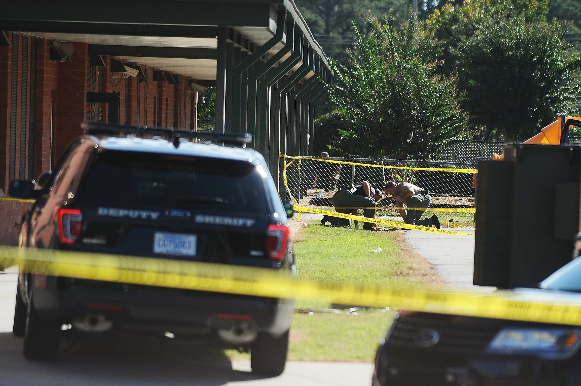 Members of law enforcement investigate an area at Townville Elementary School, where a teenager opened fire.
