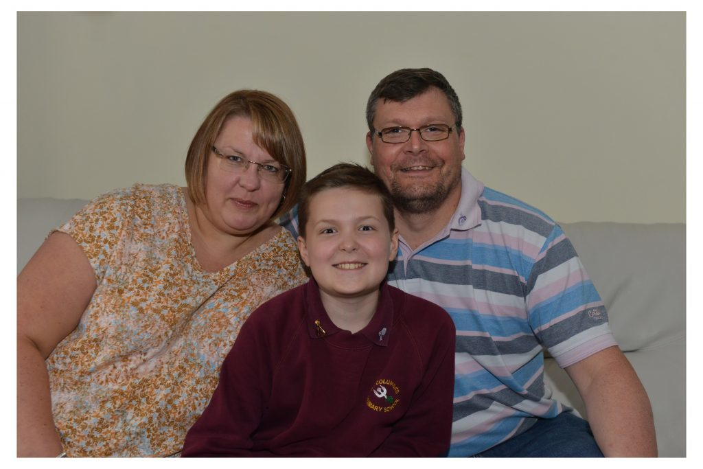 Young cancer battler Toby Etheridge with mum Alison and dad Richie