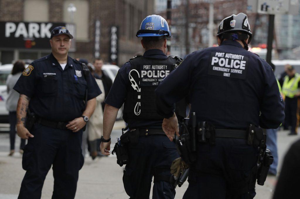 Emergency officials walk toward the Hoboken Terminal