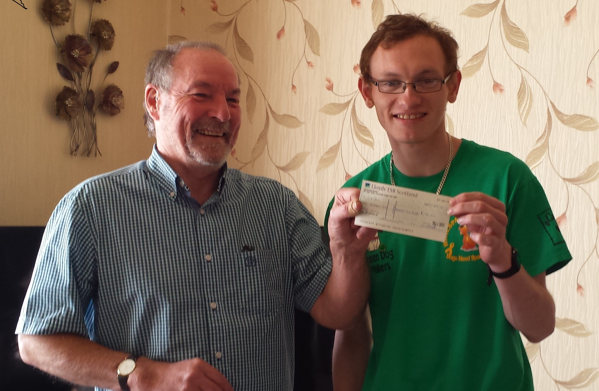 Earlier this year Scott Smith of Carnoustie Canine Capers (right) presented Peter Burke, chair of SAPALD  with a £170 cheque from the proceeds of the car boot sale.