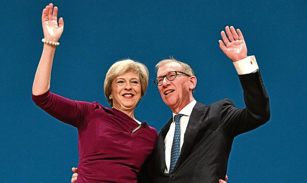 Theresa May and her Husband Philip John embrace after her speech at the Tory Party conference.