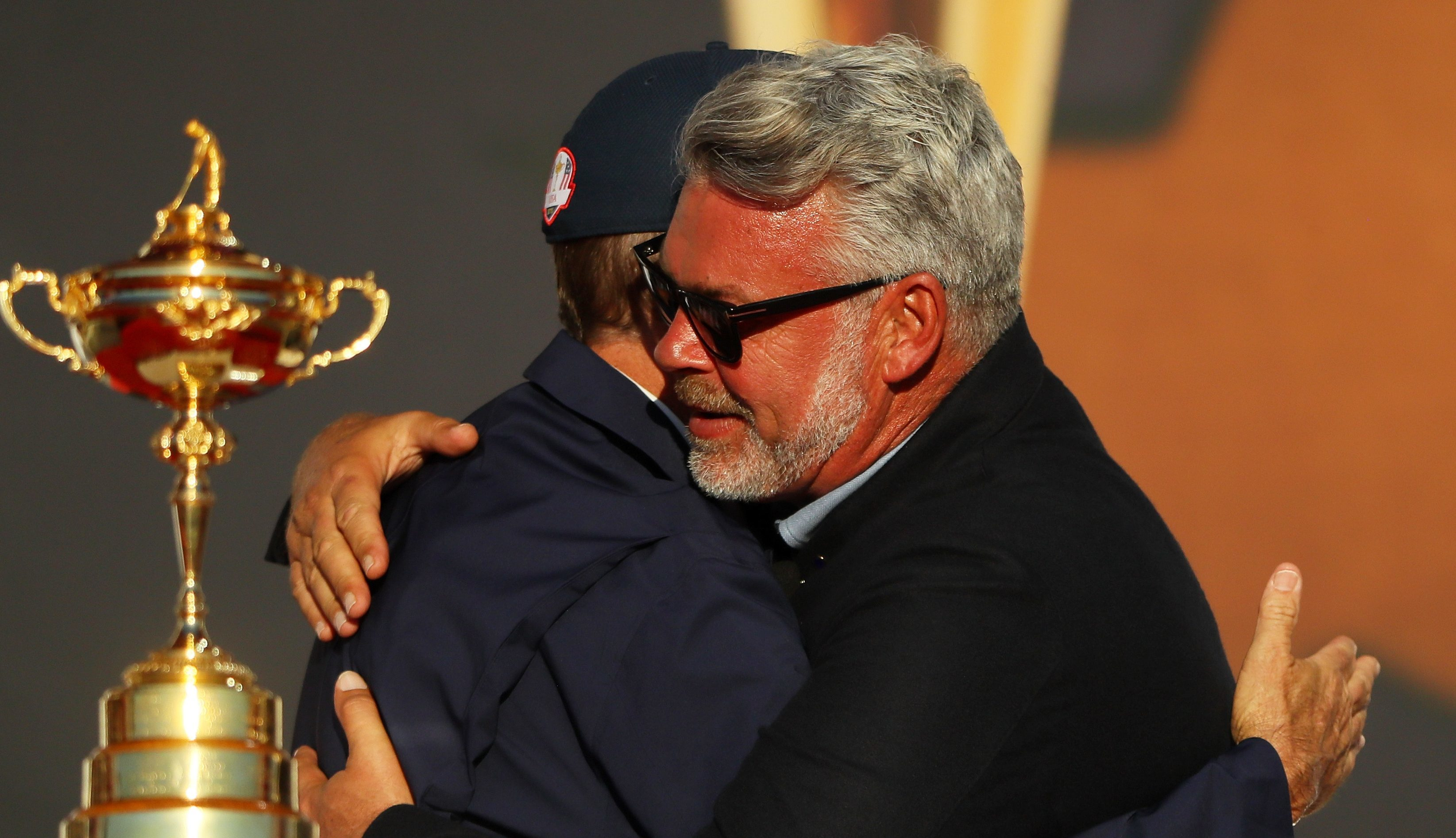 Darren Clarke embraces victorious US captain Davis Love III at the Ryder Cup closing ceremony.