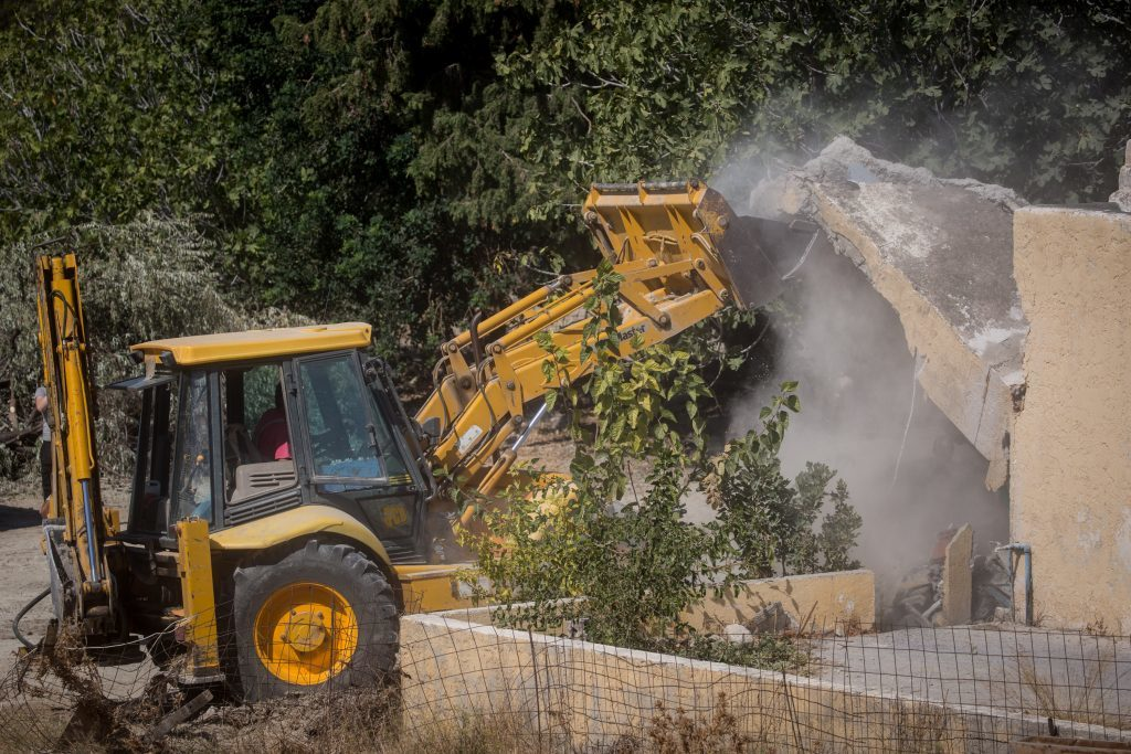 A bulldozer demolishes the last room of the farmhouse at the search site of missing toddler Ben Needham.