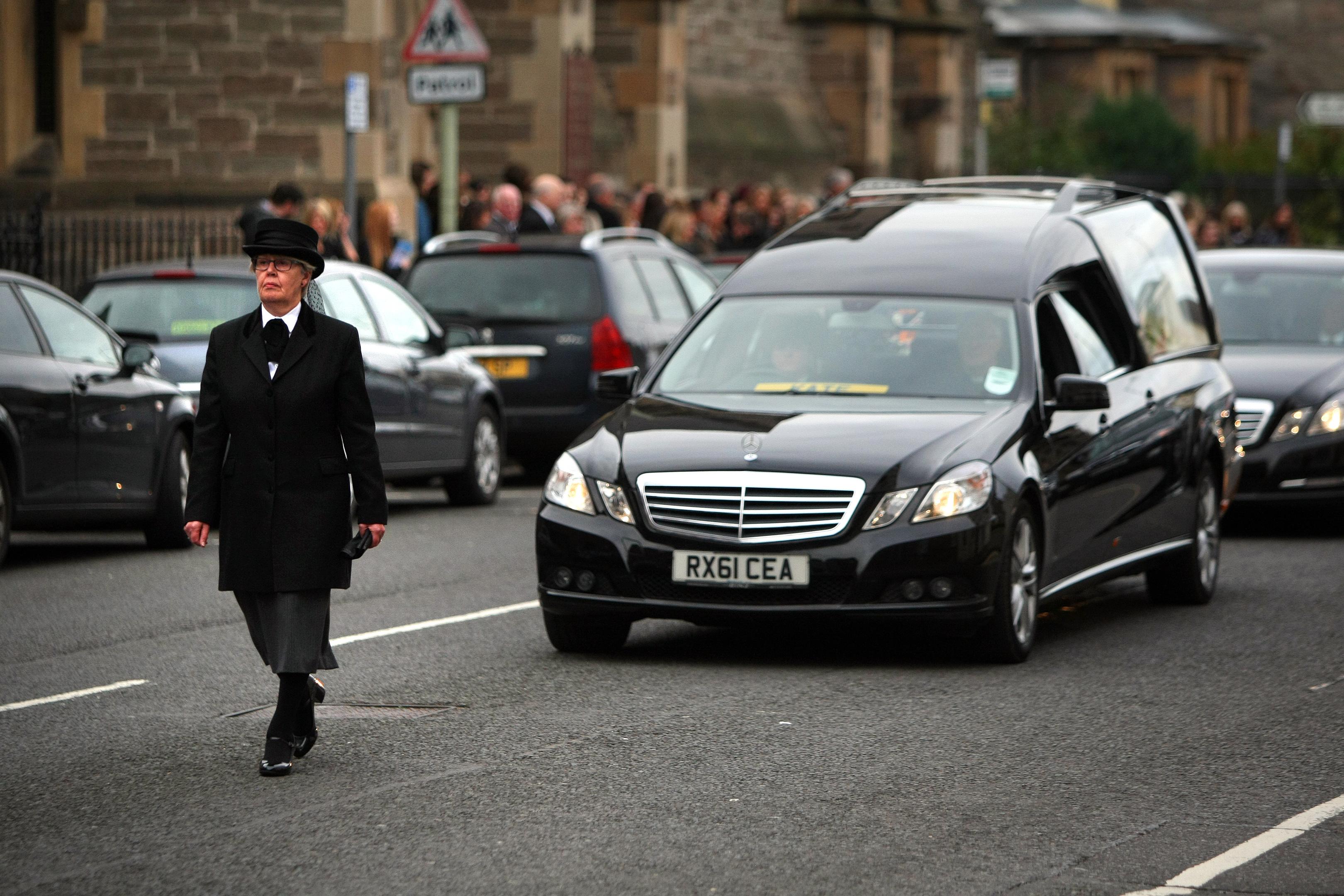 The hearse leaving the church.