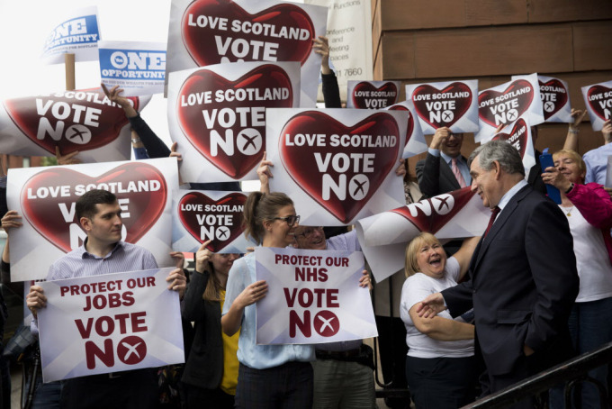 Two Yes campaign posters are held up at top left, beside a group of No campaign supporters holding up posters as former British Prime Minister and No campaigner for the Scottish independence referendum Gordon Brown, right, briefly speaks to them as he leaves after delivering a speech at a No campaign event in Glasgow on September 17, 2014