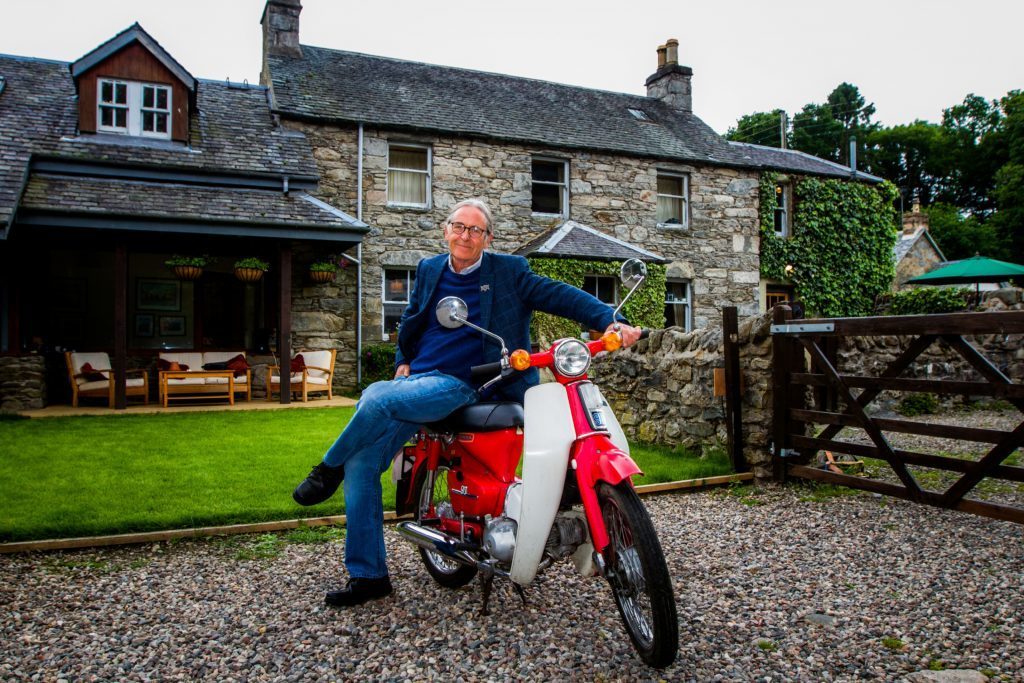 Dougie sitting on a restored Honda motorcycle outside the Old Schoolhouse in Butterstone.