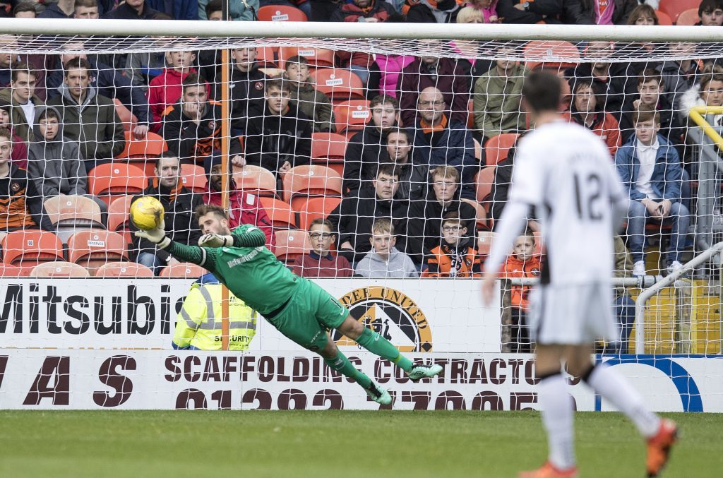 Dundee United keeper Cammy Bell makes a vital save.