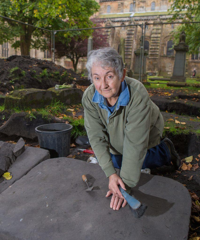 Sue Mowat uncovering gravestones.