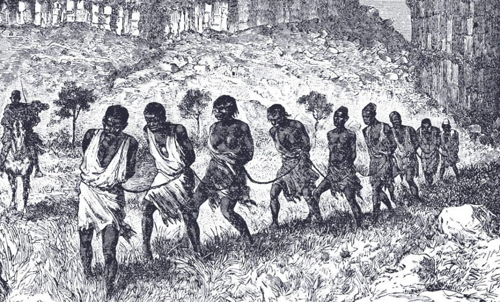 Western Sudan - A line of men and women lashed together by ropes, guarded by a horse-mounted slave trader.