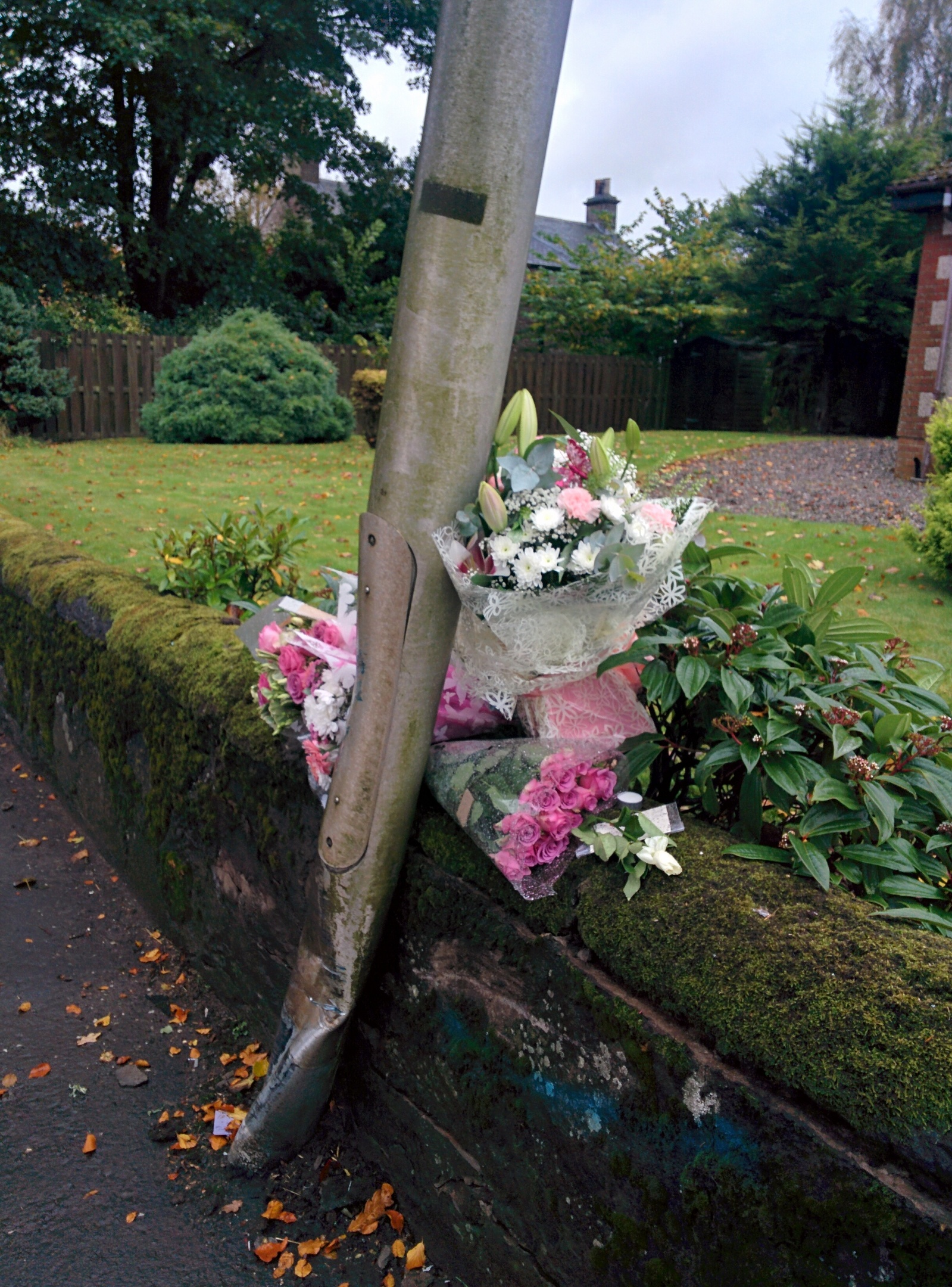 The floral tributes left beside a lampost at the scene of the fatal accident.