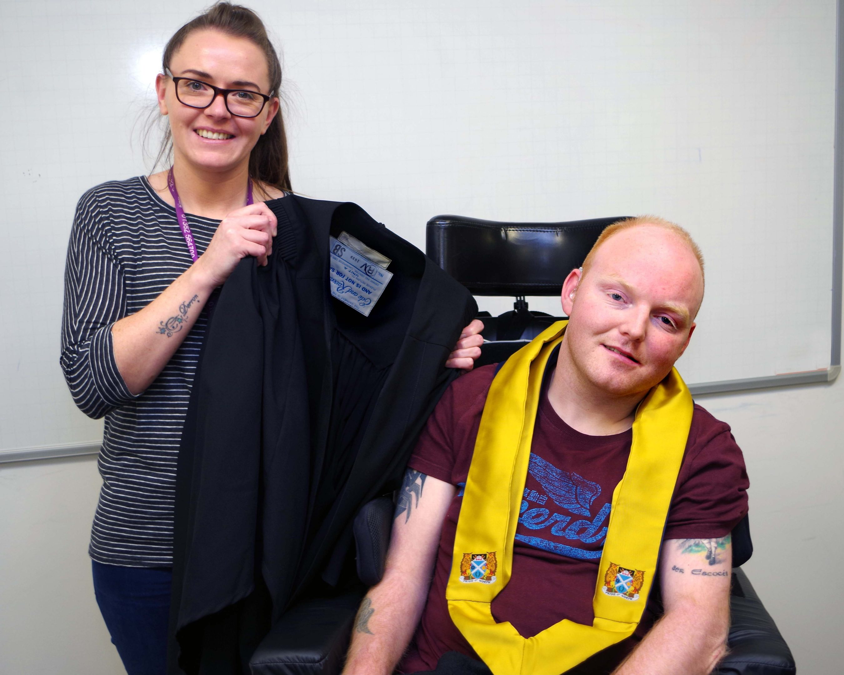 Stewart tries on a graduation robe with the help of Alanna Duncan, support worker for Gowrie Student Support.