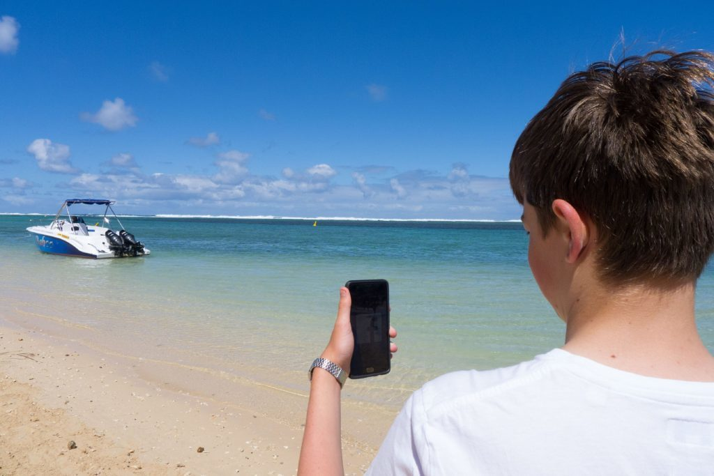 Will holding his phone in Mauritius.