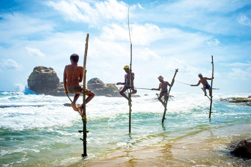 Stilt fishermen at Galle Fort Beach, Sri Lanka.