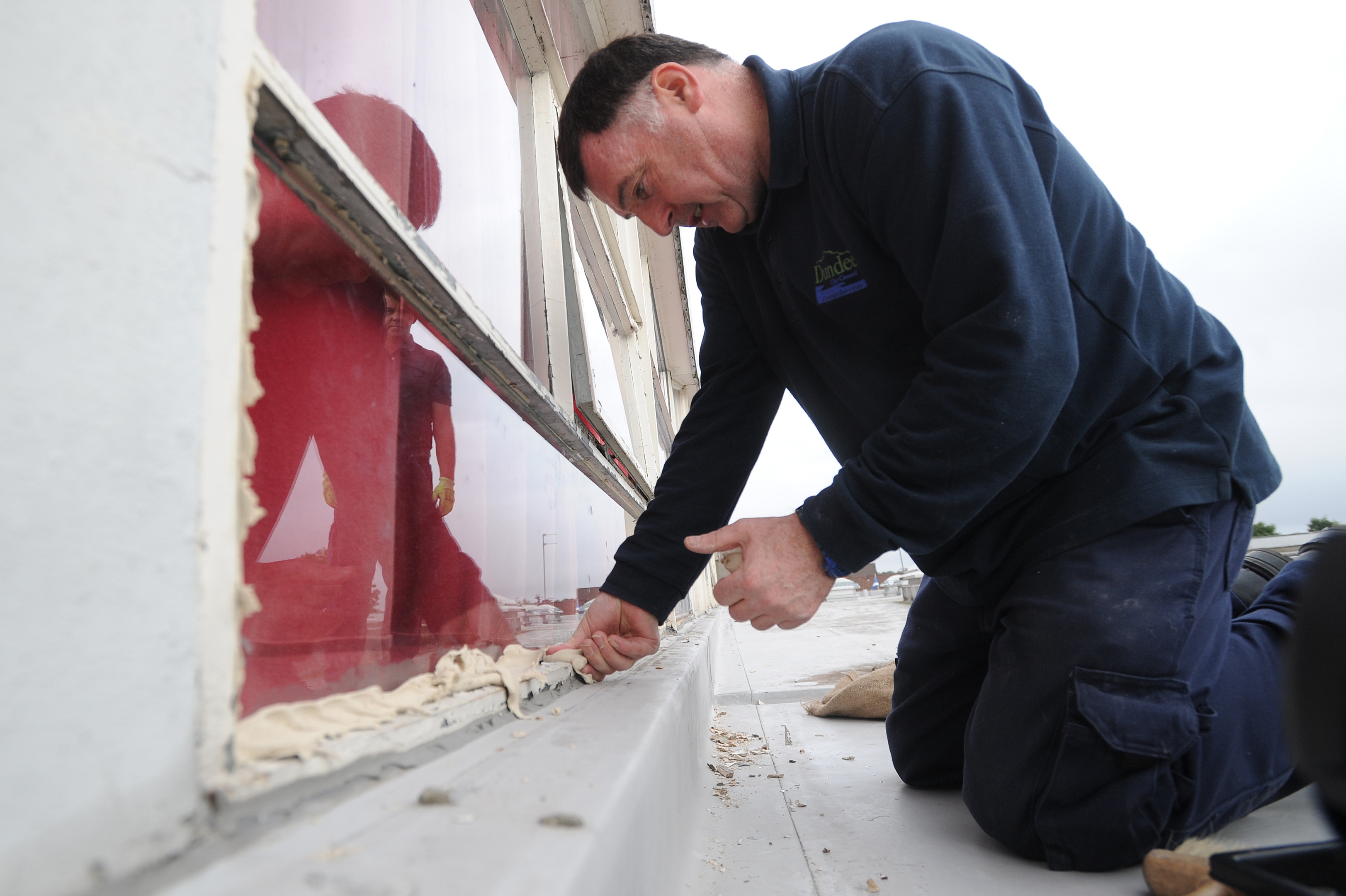 A repair man dealing with the damage inflicted by the vandals.