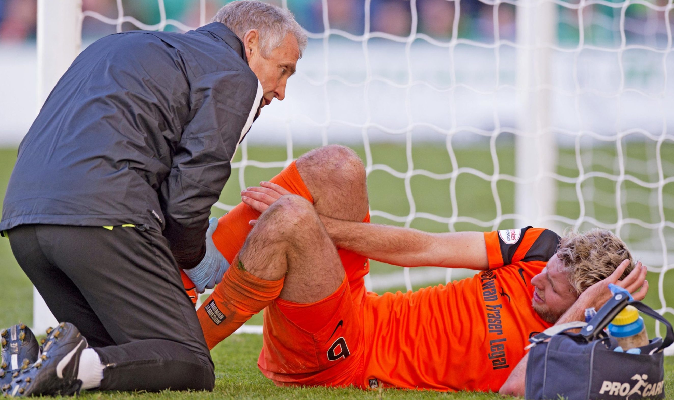 Lewis Toshney gets treatment for ankle injury during Hibs game.