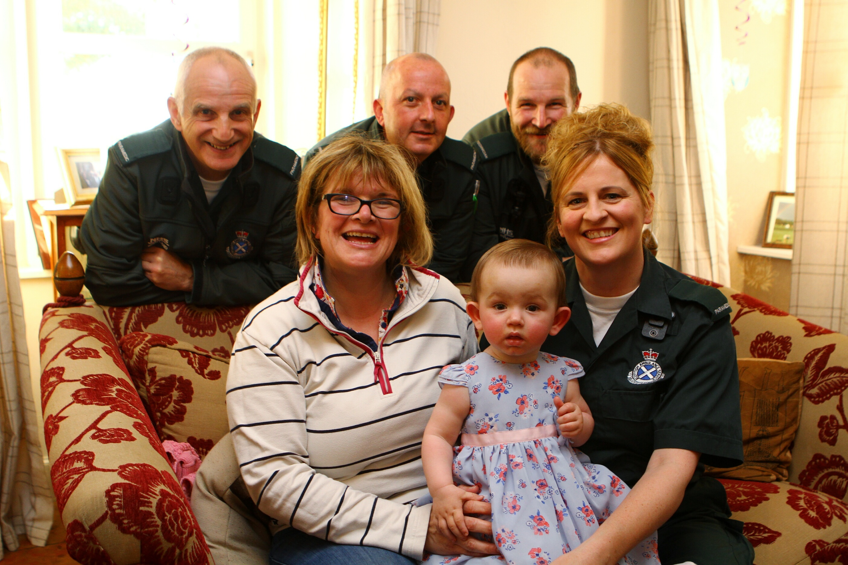 Baby Darcy Fleming celebrating her first birthday at Peel Farm with mum Claire and Paramedics Angie McKenzie, and back L/R, Stuart Parker, Stuart Wilkie,  and Steven Dryden.