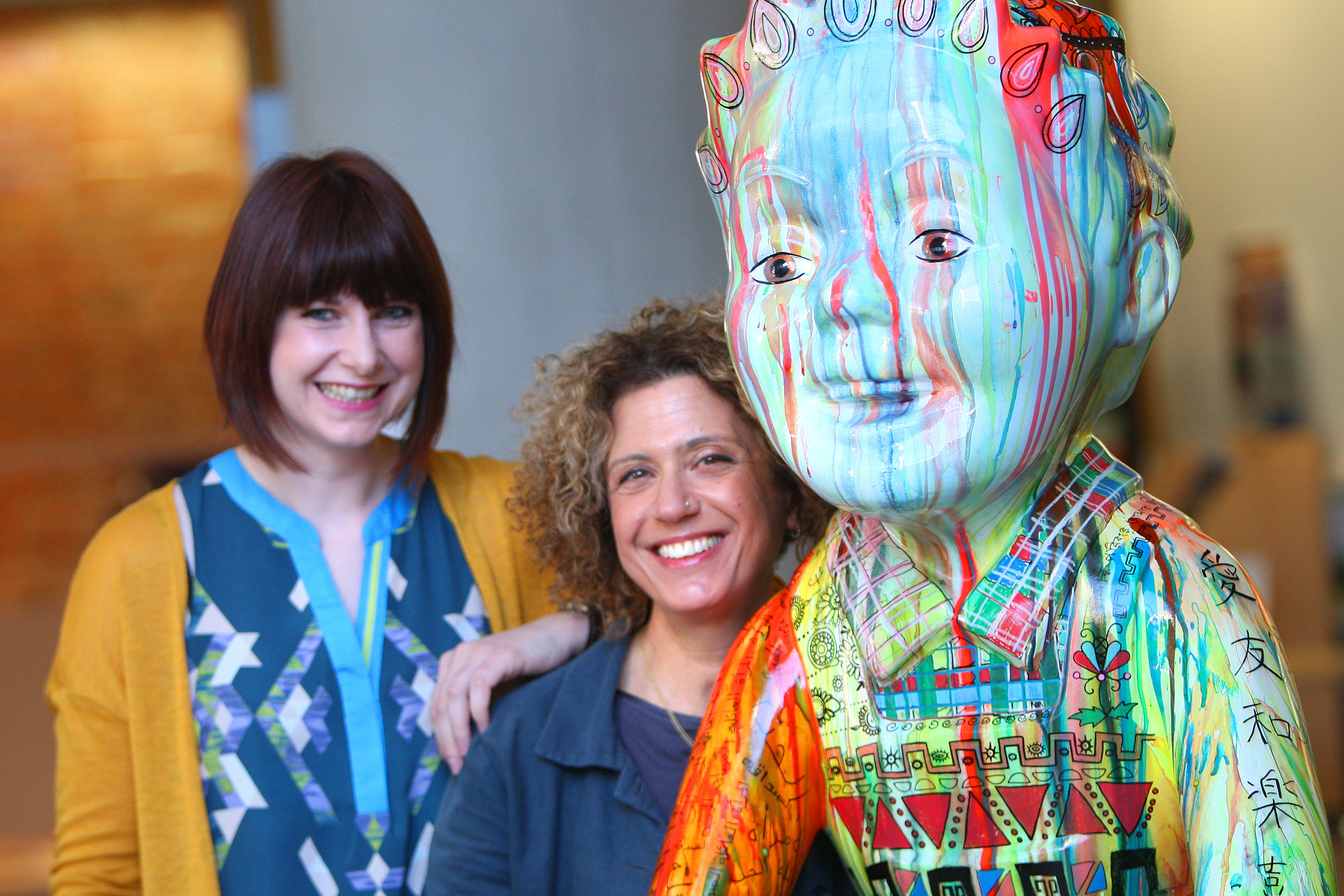 Dundee International Women's Centre illustrator and project support worker Laura Darling and trustee Vered Hopkins welcome the statue to Dundee House.