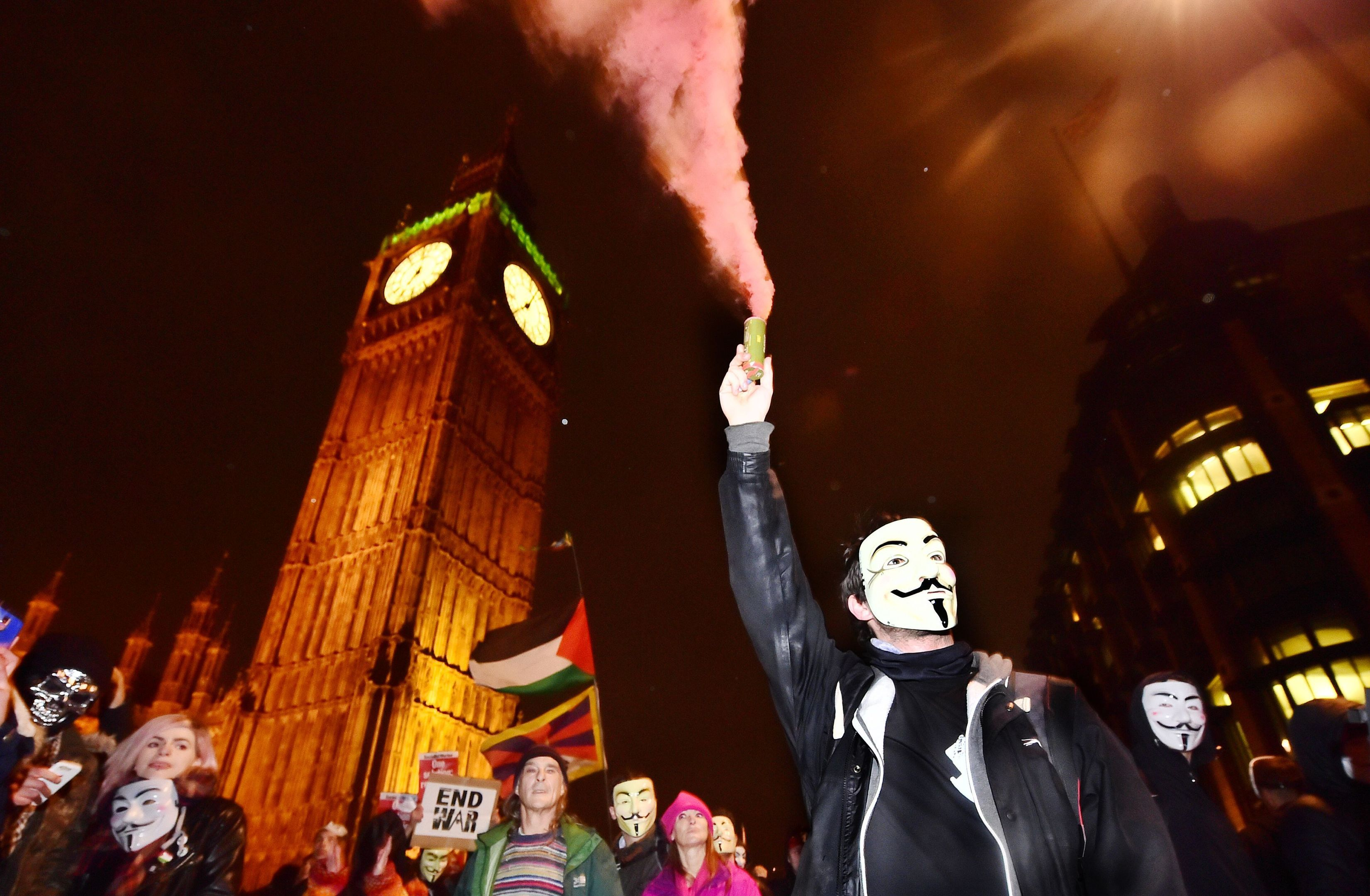 Protestors demonstrate near the Houses of Parliament in London, during the Million Mask March bonfire night protest organised by activist group Anonymous in 2015