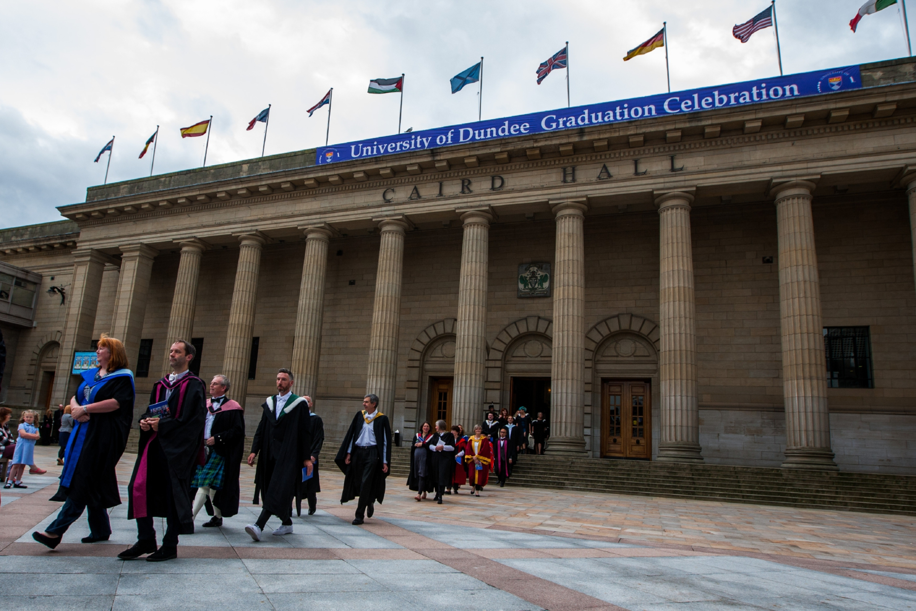 Graudates and University staff exit into the square after last year's Summer Graduation