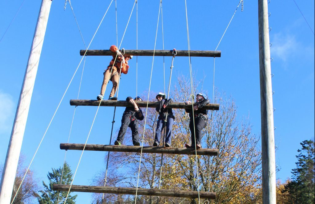 Gayle climbs up the suspended ladder, flanked by scout leaders.