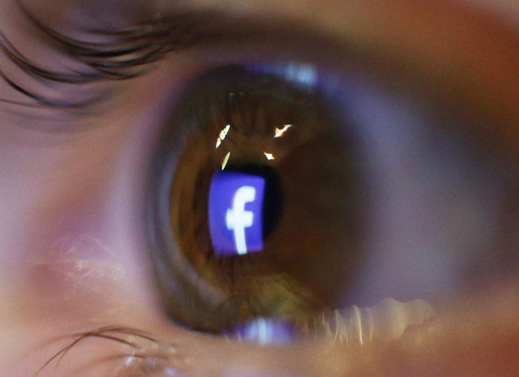 The logo of social media and networking site Facebook is reflected in an eye, in London.