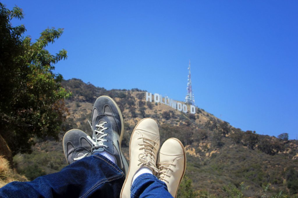 A couple relaxing by the Hollywood sign.