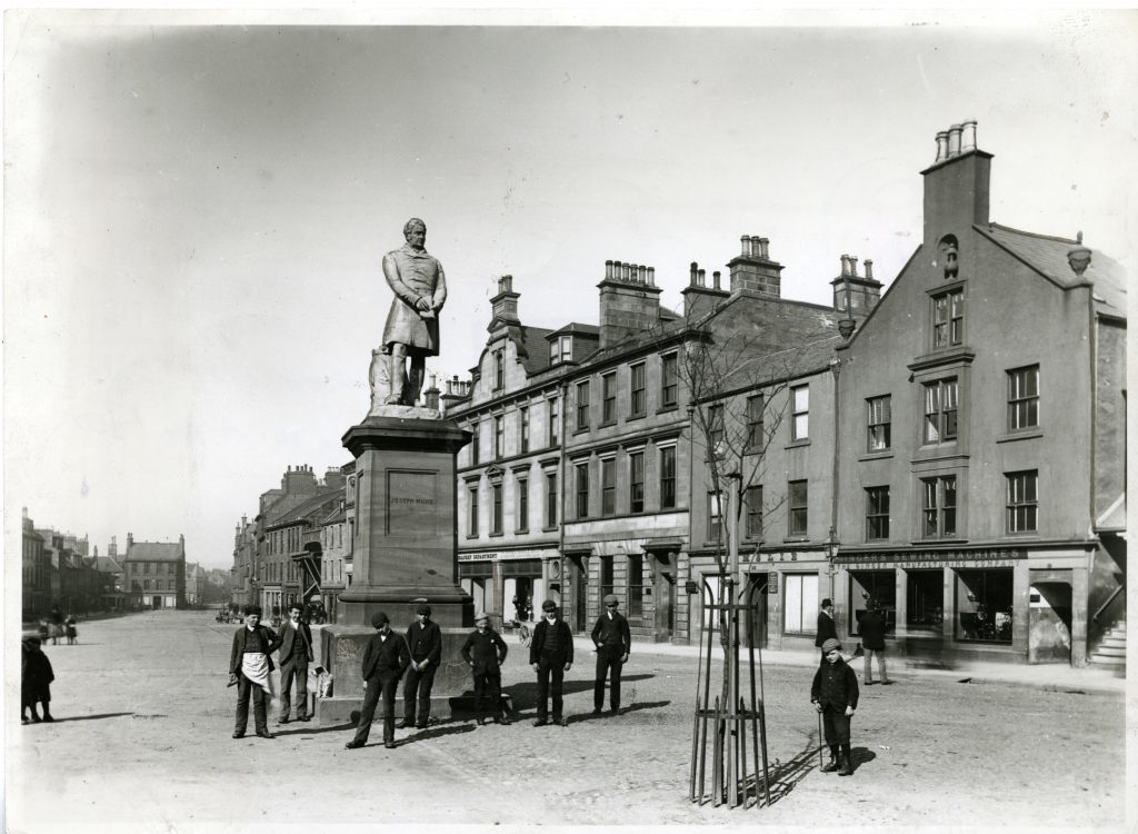 Photograph showing a group of men standing beside the Joseph Hume Statue in Montrose High Street. April 11 1892.