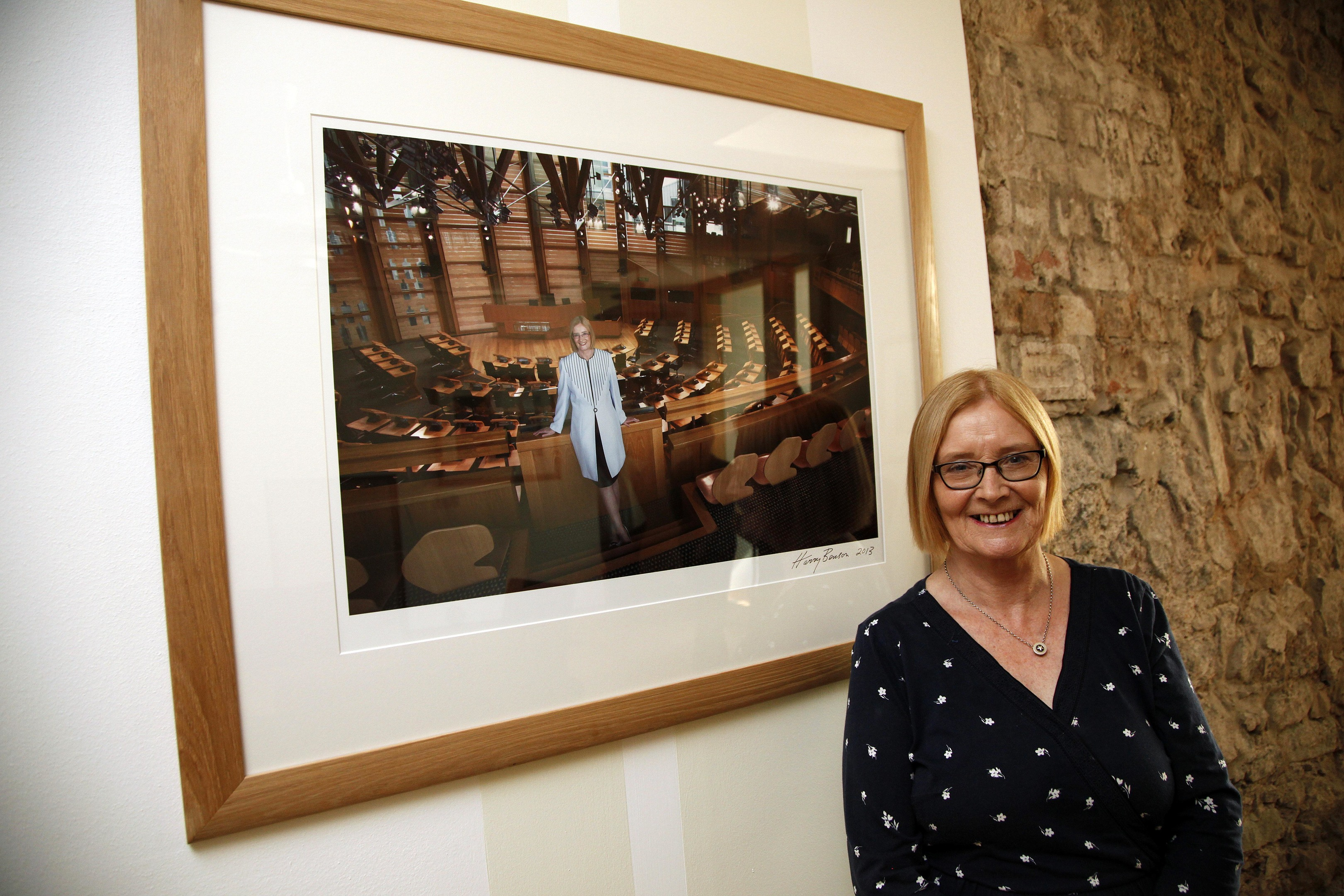Tricia Marwick, standing with her official presiding officer portrait.