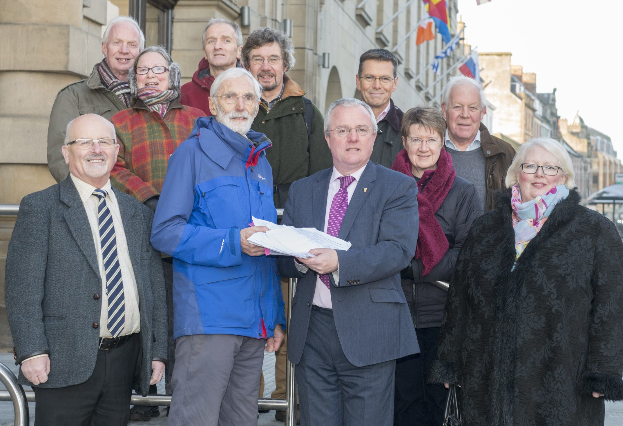 Dr Jim Young, centre, handing the Dundee Road traffic light petition to councillor Peter Barrett