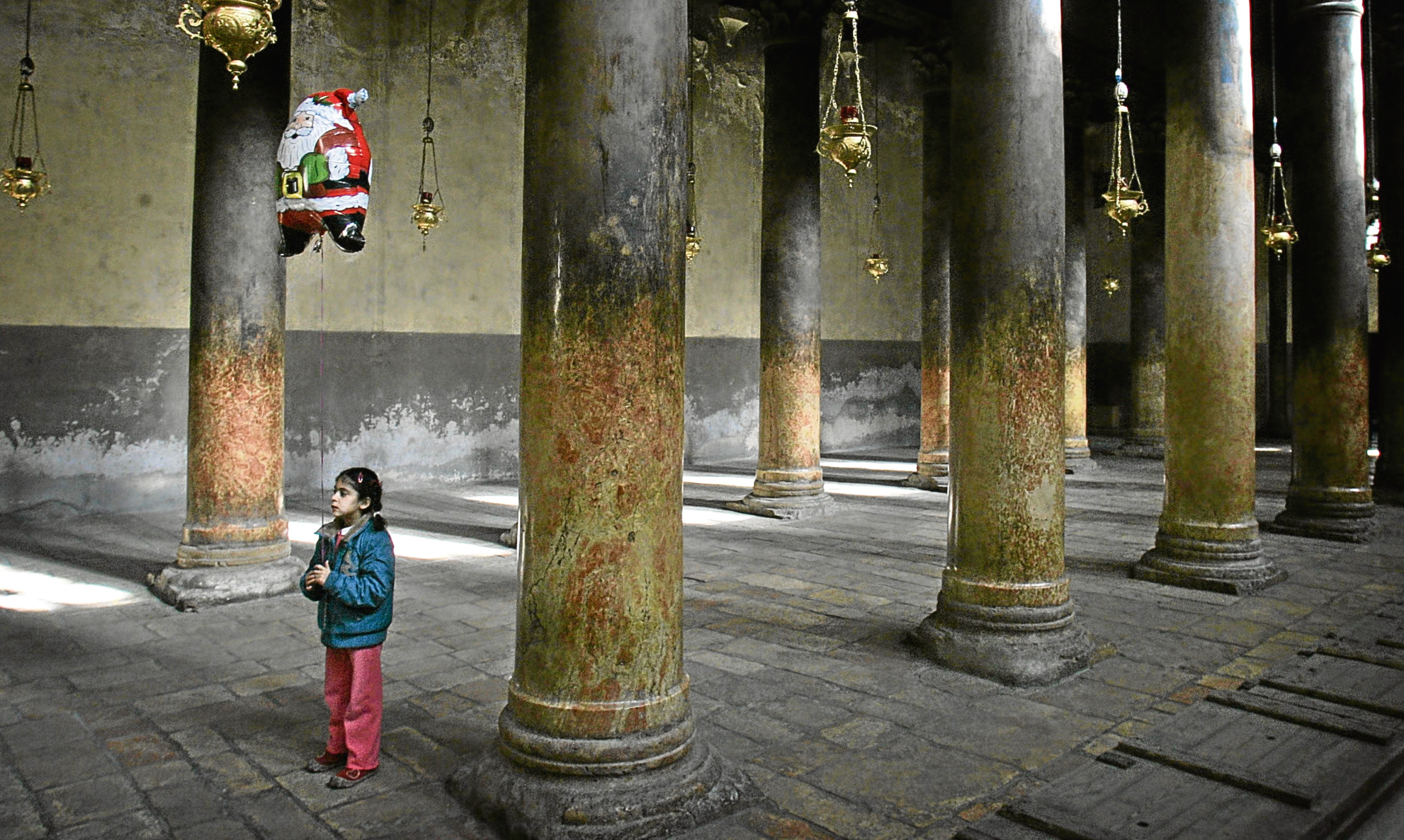 A Palestinian Christian girl holds a Santa Claus-shaped balloon as she stands in the Church of the Nativity in Bethlehem.