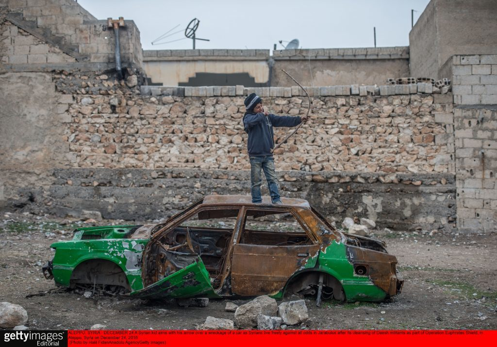 A Syrian kid aims with his arrow over a wreckage of a car
