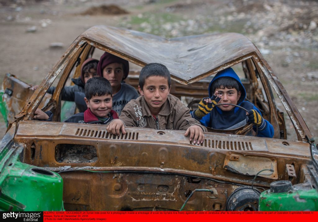 Syrian kids pose for a photograph inside a wreckage of a car