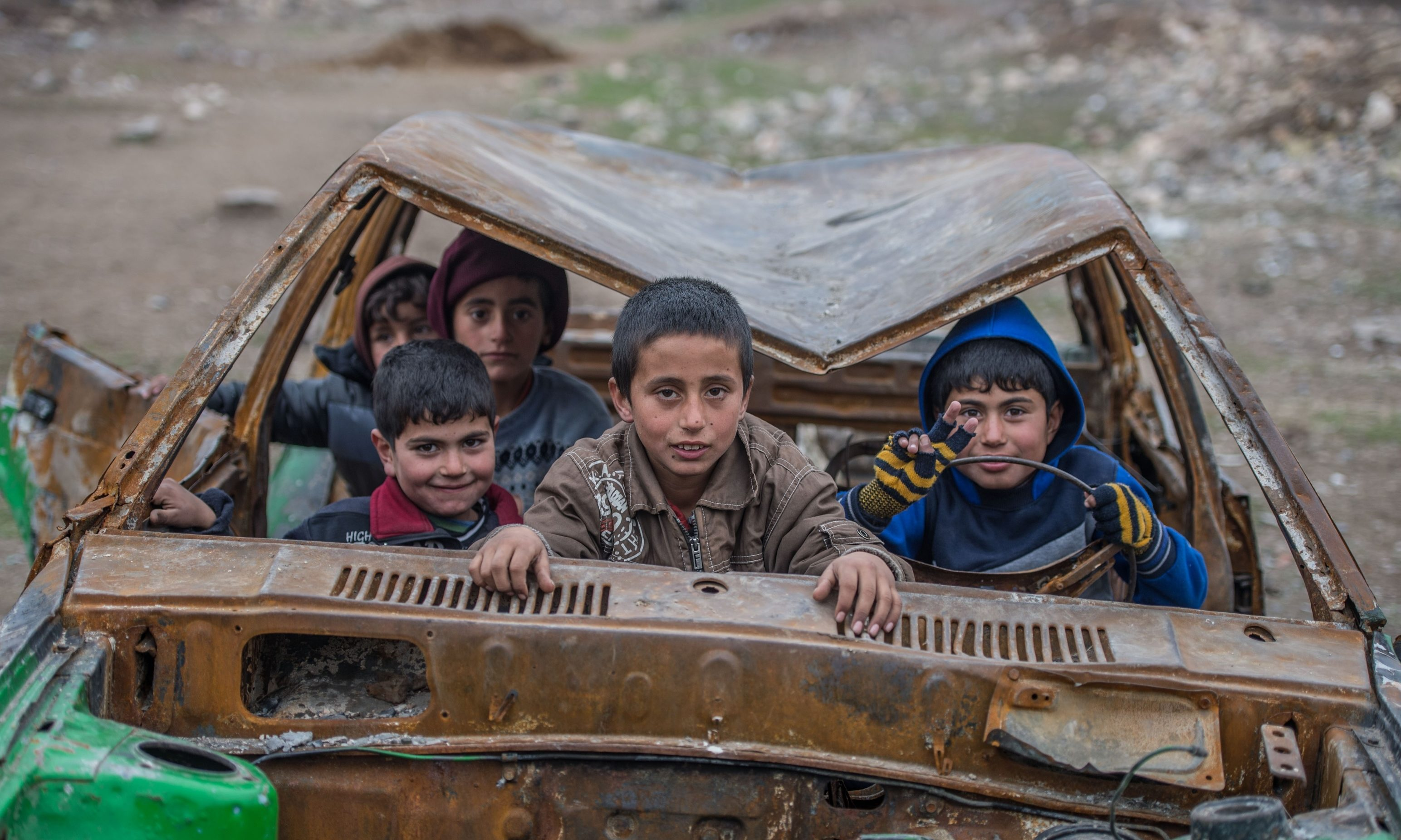 Syrian kids pose for a photograph inside a wreckage of a car in 2016
