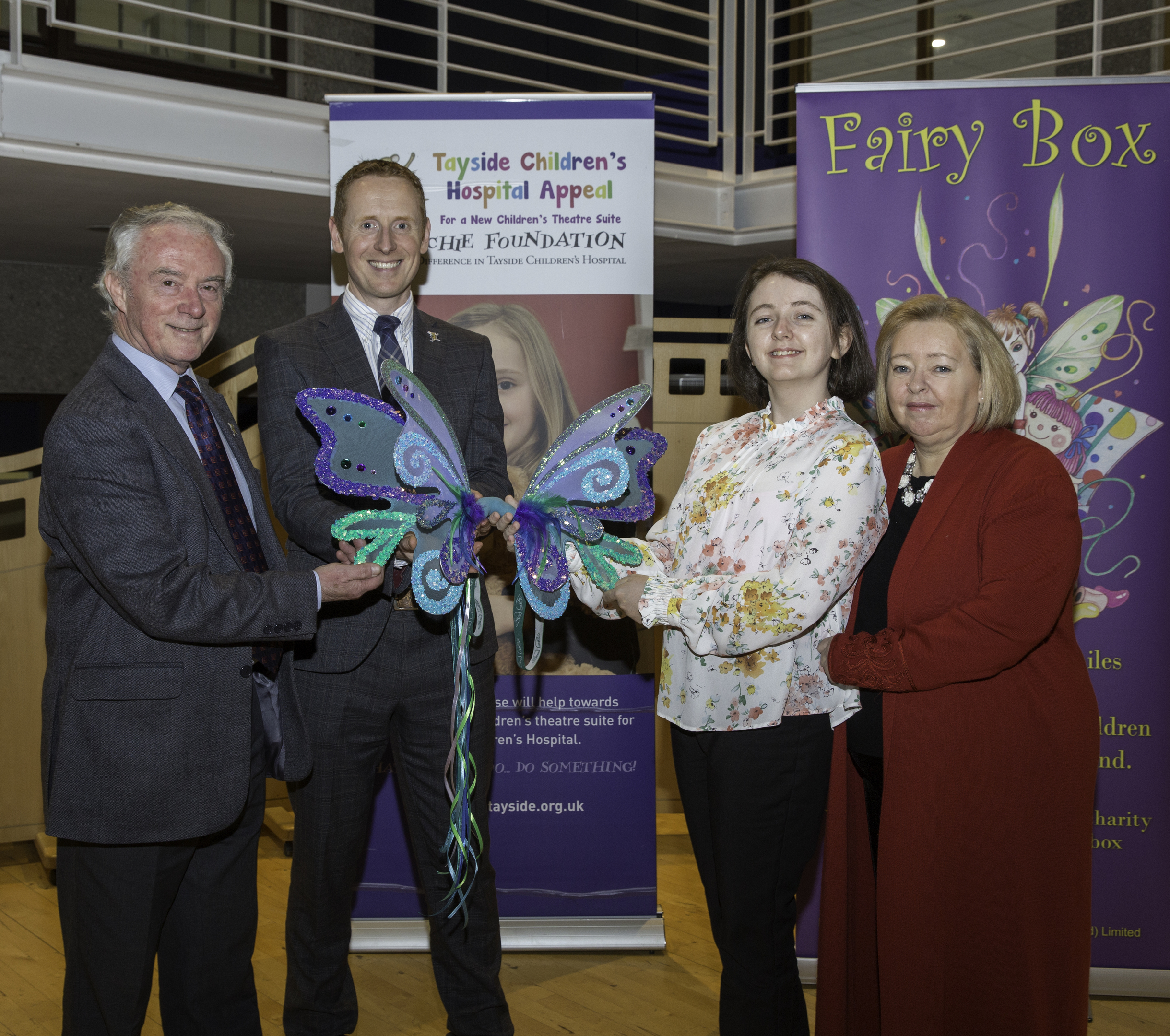 L-R Joe Mackie, chairman, and David Cunningham, chief executive of The ARCHIE Foundation accept the fairy wings from Aimee and Rosemary Butler