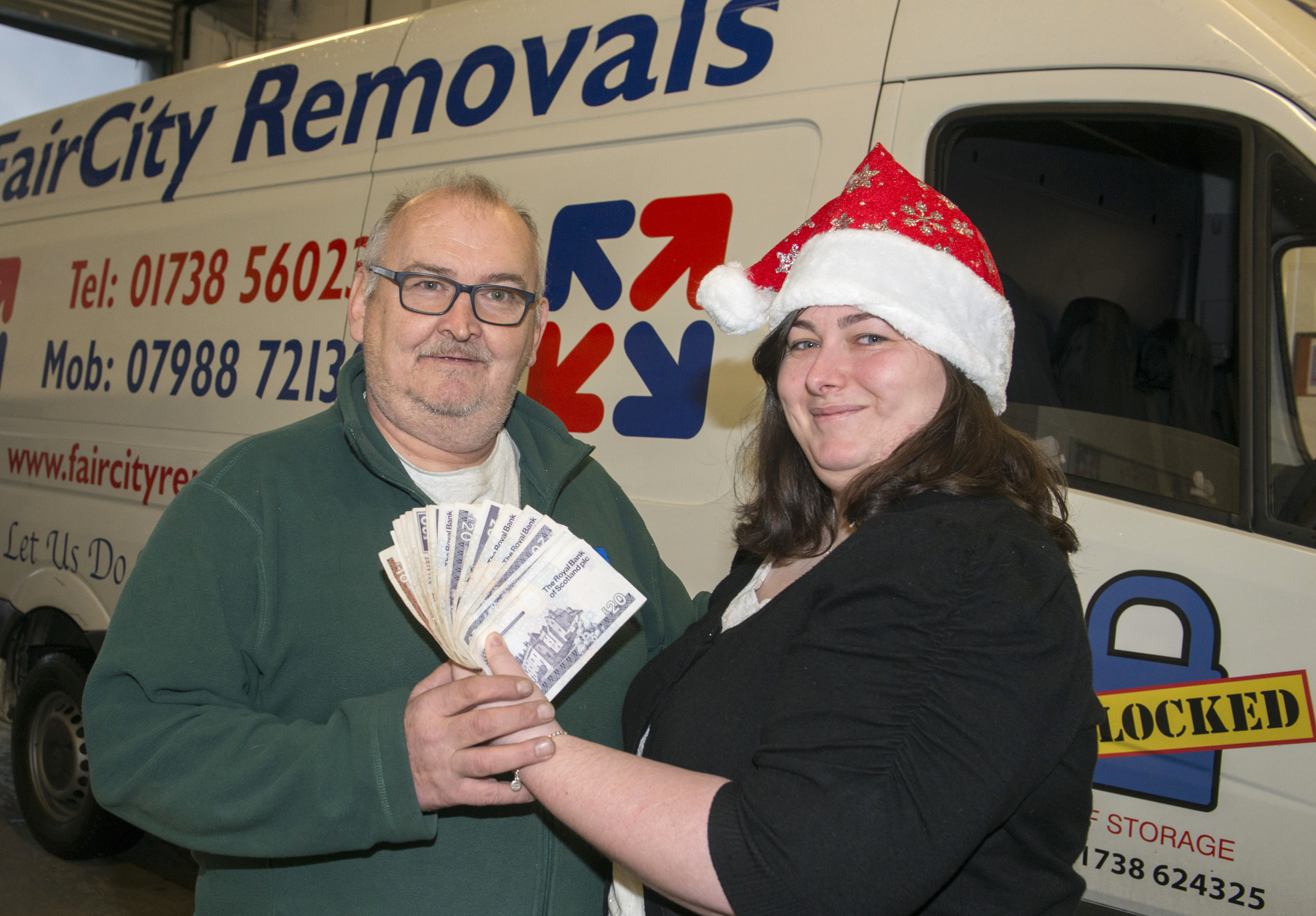 Kirsty McIntosh hands over some of the cash  to Jim Melville.
